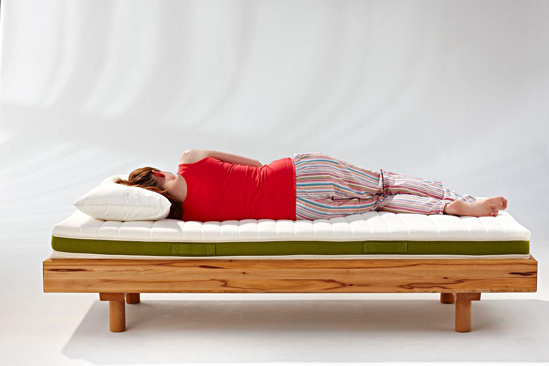 Frau schläft auf Multidorma im Massivholzbett